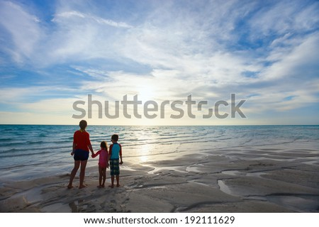 Silhouettes of mother and two kids at tropical beach enjoying sunset during summer vacation - stock photo