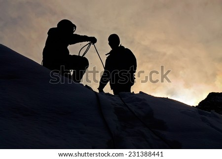 Silhouettes of mountaineers working with rope in sunset