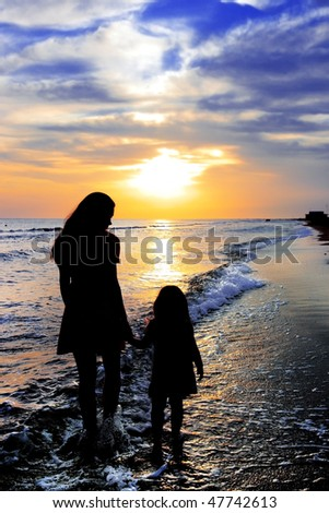 Silhouettes of mum and the little girl against a sea sunset - stock photo