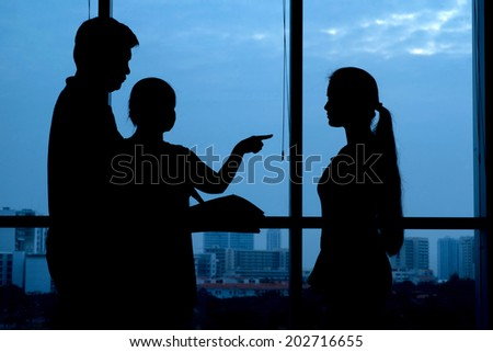 Silhouettes of parents arguing with their teenage daughter - stock photo