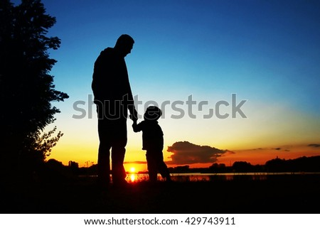 Silhouettes of parents with baby on sunset background - stock photo