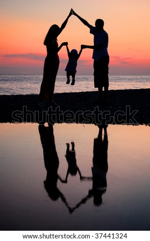 Silhouettes of parents with child against  sea decline - stock photo