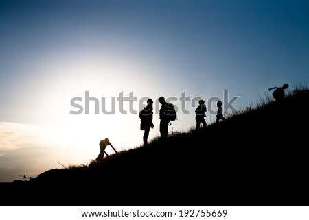 Silhouettes of parents with children rising uphill - stock photo