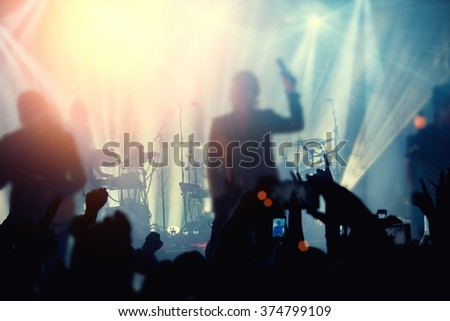 Silhouettes of people and musicians in big concert stage. Bright beautiful rays of light - stock photo