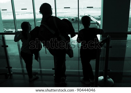 Silhouettes of people at airport - stock photo