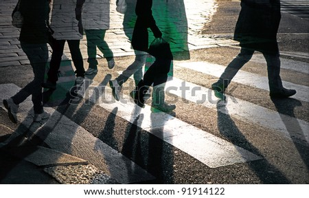 Silhouettes of people at pedestrian crossing - stock photo