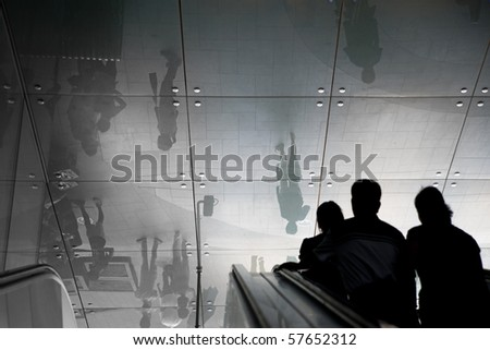 Silhouettes of people coming up an escalator, with reflection of the outside world  in the ceiling - stock photo