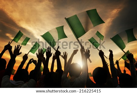 Silhouettes of People Holding Flag of Nigeria - stock photo