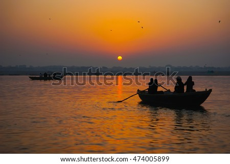 Silhouettes of people in tourist boats at holy Ganga river and rising sun in the early foggy morning, at sunrise, in Varanasi, or ancient Benares city, India. Landscape, could be used as background.