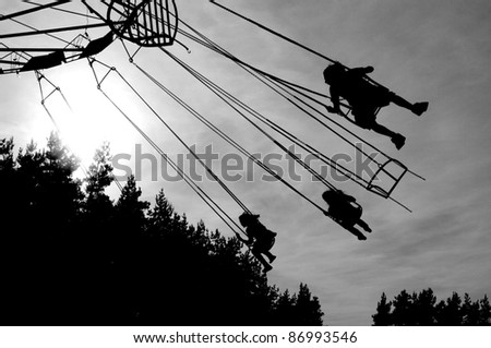 Silhouettes of people on a swing chain - stock photo