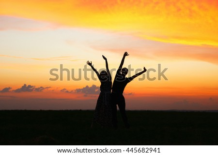 Silhouettes of people on bright evening sunset.