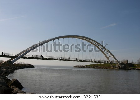 Silhouettes of people on pedestrian bridge - stock photo