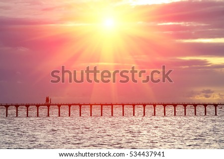 Silhouettes of people on the bridge over the sea on a sunset