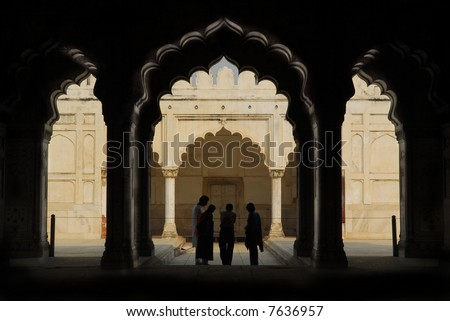 silhouettes of people under the arches at the red fort in delhi, india - stock photo