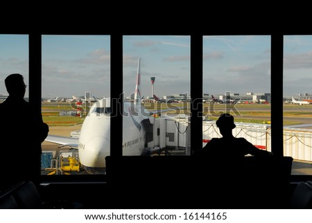 silhouettes of people waiting at the airport for their flight - stock photo