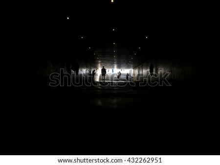 Silhouettes of people walking in pedestrian tunnel - stock photo