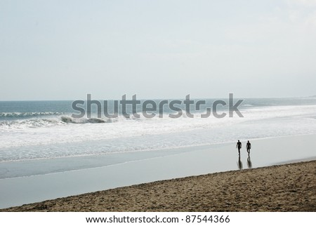 Silhouettes of people walking on the beach. Bali. Indonesia - stock photo