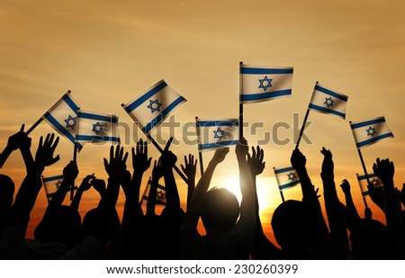 Silhouettes of People Waving the Flag of Israel - stock photo