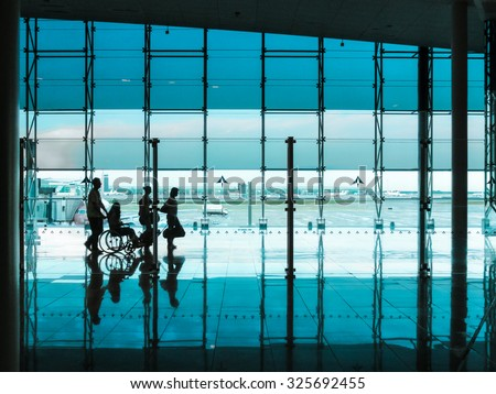 Silhouettes of people with luggage walking at airport. - stock photo