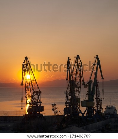 Silhouettes of port cranes on a background of rising sun - stock photo