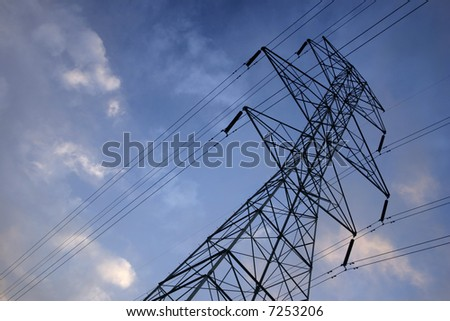 Silhouettes of power lines and a tower with a deep blue sky - stock photo