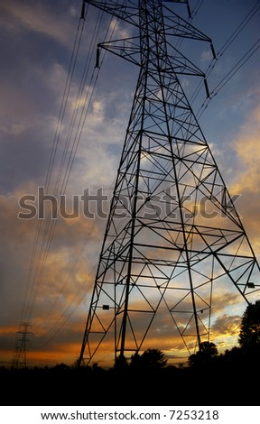Silhouettes of power lines and towers with a brilliant sunset