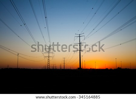 Silhouettes of power transmission line poles and system of cables against beautiful colorful sunset (night shot, sunset lighting, focus on large poles)