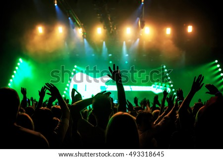 silhouettes of rock concert crowd in front of bright stage lights, green guitar on stage