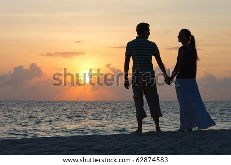 Silhouettes of romantic couple on tropical beach at sunset