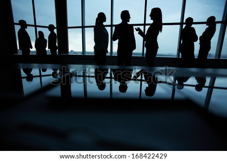 Silhouettes of several colleagues communicating in office - stock photo