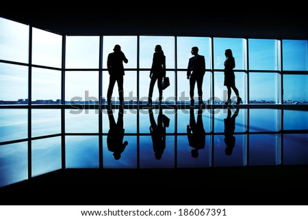 Silhouettes of several office workers standing by the window and looking at their colleague speaking on the phone - stock photo