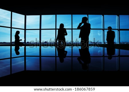 Silhouettes of several office workers working on background of window - stock photo