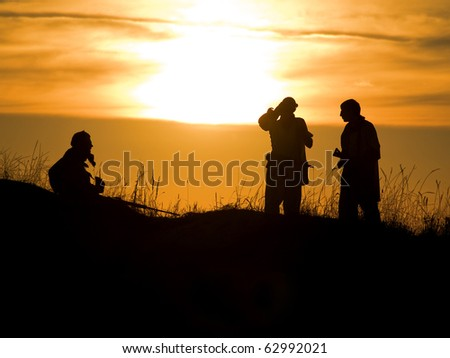 Silhouettes of several soldiers with rifles against a sunset - stock photo