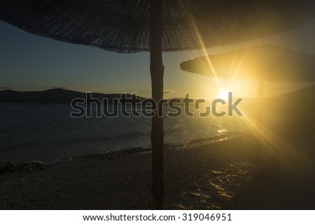 Silhouettes of straw parasols with wooden legs on scenic waterfront with pebble beach calm sea low hills in distance at sunset, horizontal photo - stock photo