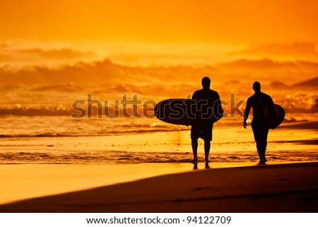 Silhouettes of Surfers on the Beach at Sunset - stock photo