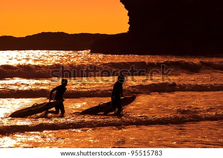 Silhouettes of surfers walking out of the sea - stock photo