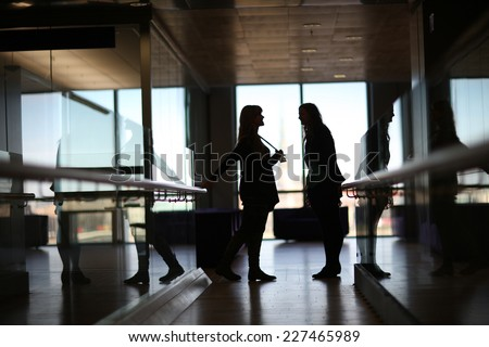 Silhouettes of talking women in the office corridor - stock photo