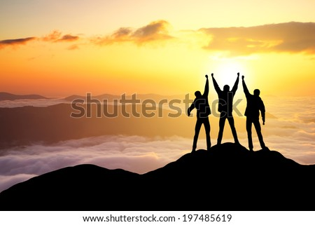 Silhouettes of team on mountain peak. Sport and active life concept - stock photo