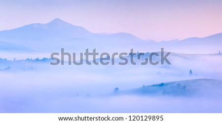 Silhouettes of the mountains in the morning mist. Summer, sunrise - stock photo