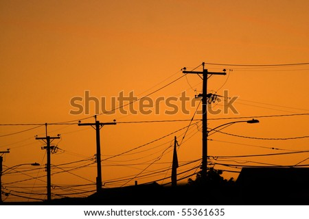 Silhouettes of the power lines and wires in a residential neighborhood back-lit by the evening sky. - stock photo