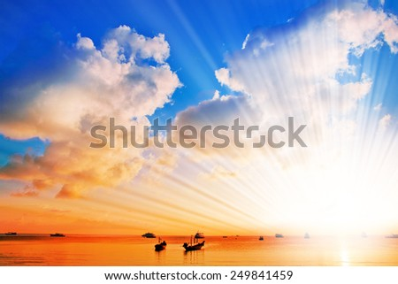 Silhouettes of the ships and boats in the sunset sky - stock photo