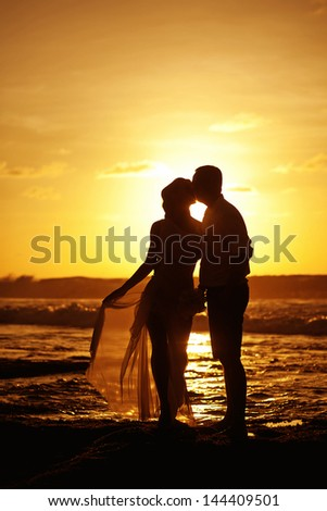 silhouettes of the wedding couple in evening, bali - stock photo