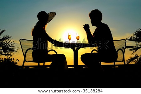 Silhouettes of the woman and man sit at a table on sundown - stock photo
