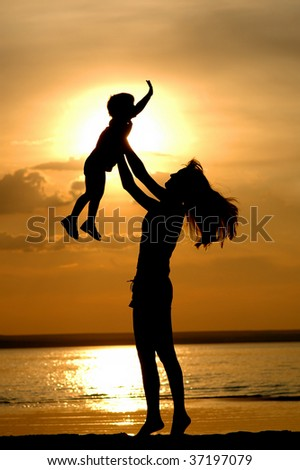 Silhouettes of the women and child on sundown - stock photo