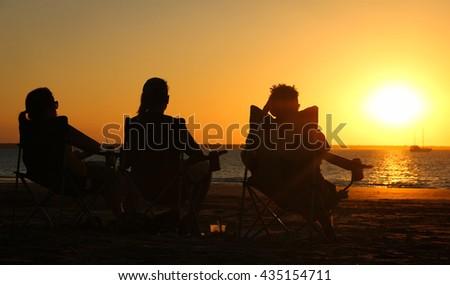 Silhouettes of three friends peacefully enjoying a wonderful sunset on Mindil Beach, in Darwin, Northern Territory, Australia - stock photo