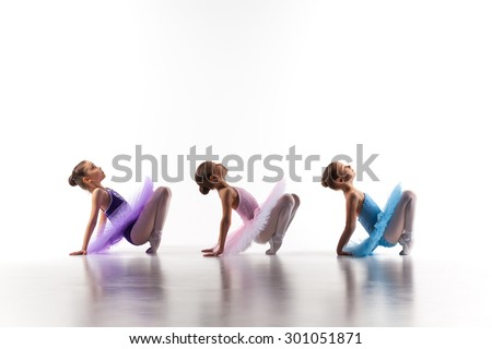 Silhouettes of three little ballet girls sitting in ballet pose in multicolored tutu and pointe shoes together on white background - stock photo