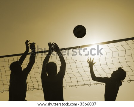 Silhouettes of three men playing beach volleyball, - stock photo
