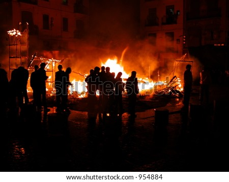 Silhouettes of tourist crown in front of rubble from burning statue at las fallas in Valencia spain