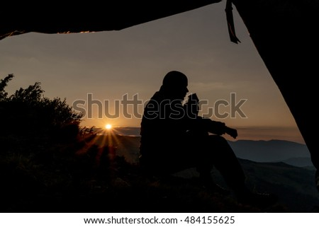 Silhouettes of tourists with a cup of tea in hand on background of mountains. The view from the open tent