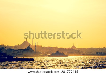 Silhouettes of turkish steamboat and minaret of mosque in Istanbul on sunset. Skyline with soft light effect - travel concept in retro style. Cityscape of old town in a fog, Istanbul seaside. - stock photo